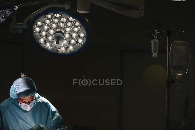 Cirurgião em máscara operando sob lâmpada — Fotografia de Stock