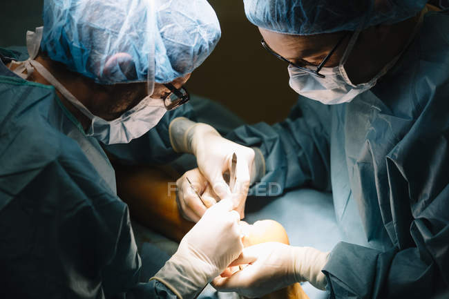 Two surgeons while operating patient — Stock Photo