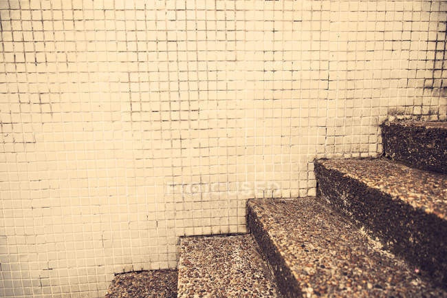 Cropped image view of shabby granite steps and tiled wall — Stock Photo