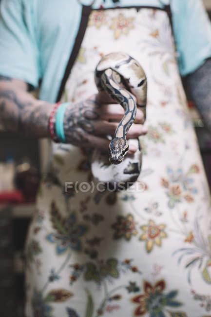 Hombre tatuado sosteniendo una serpiente grande . - foto de stock