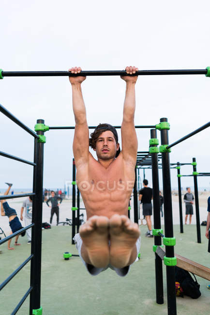 Muscular man exercising on chin-up bar — Stock Photo