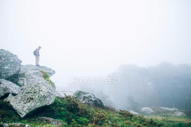 Hombre de pie sobre roca - foto de stock