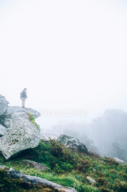Человек стоит на скале — стоковое фото