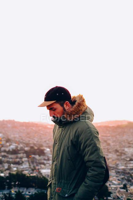 Homme au manteau sur fond de paysage urbain — Photo de stock