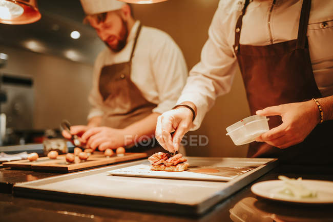 Cooks preparing dishes in kitchen — Stock Photo