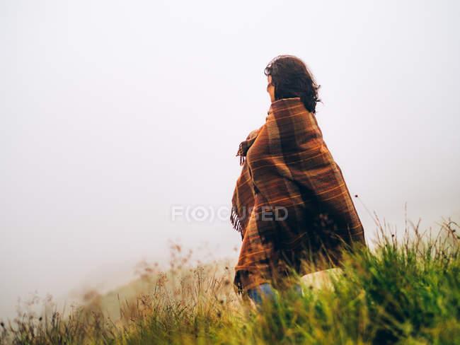 Fille en couverture contre du ciel brumeux — Photo de stock