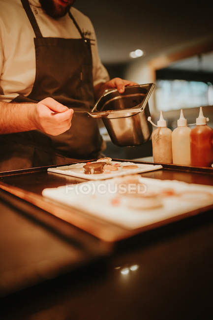 Cook dribbling sauce on dish — Stock Photo