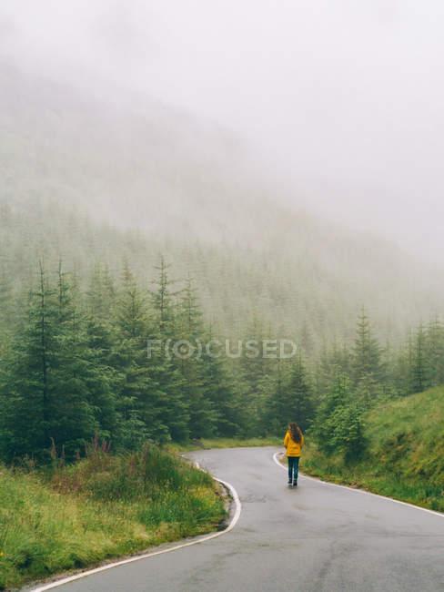 Mädchen zu Fuß kurvige Straße — Stockfoto