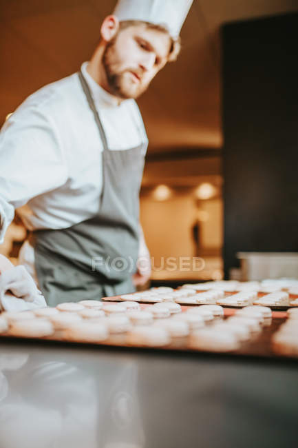 Cook looking at tray with cookies — Stock Photo