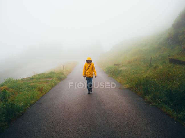 Female tourist in raincoat walking on foggy road — Stock Photo