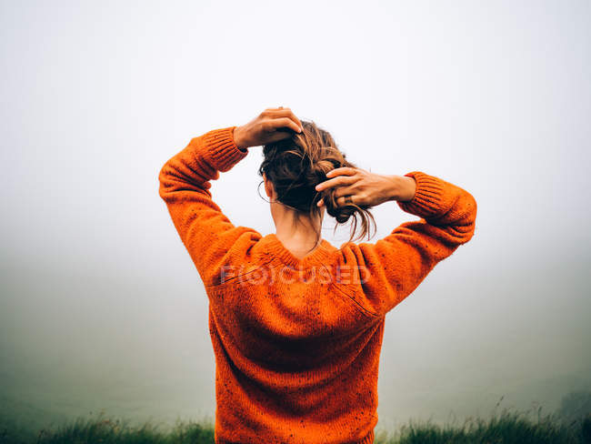 Girl adjusting hair over fog — Stock Photo