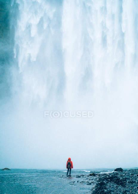 Persona in piedi contro potente cascata — Foto stock