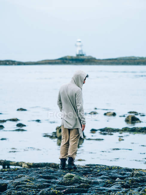 Homme sur la côte de pierre contre de phare sur l'île . — Photo de stock