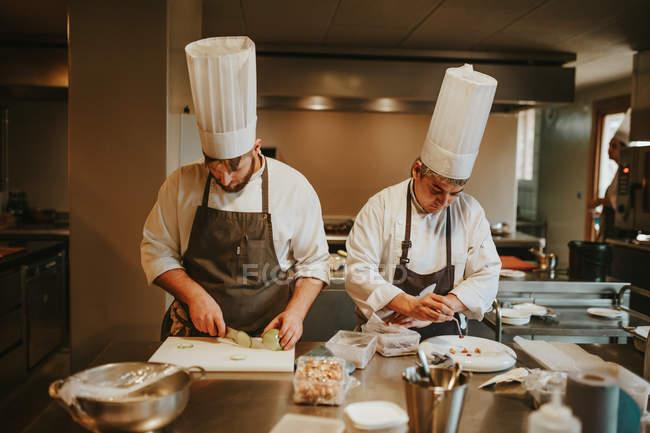 Cozinheiros que servem pratos — Fotografia de Stock