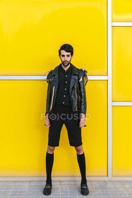 Uomo di moda posa su parete gialla — Foto stock