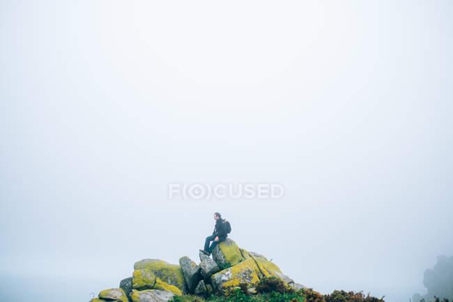 Hombre sentado en la formación de rocas . - foto de stock