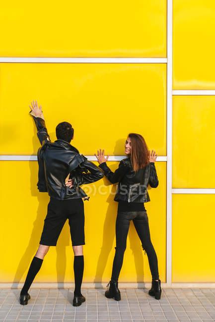 Мода пара позують над жовті стіни — стокове фото