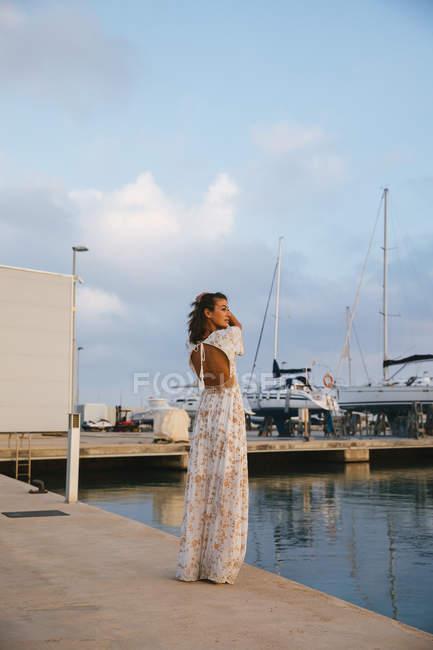 Женщина стоит и смотрит через плечо — стоковое фото