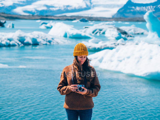 Girl with analog camera standing over water — Stock Photo