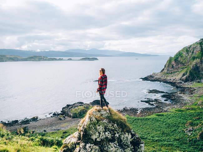 Menina na rocha e olhando para o lago — Fotografia de Stock