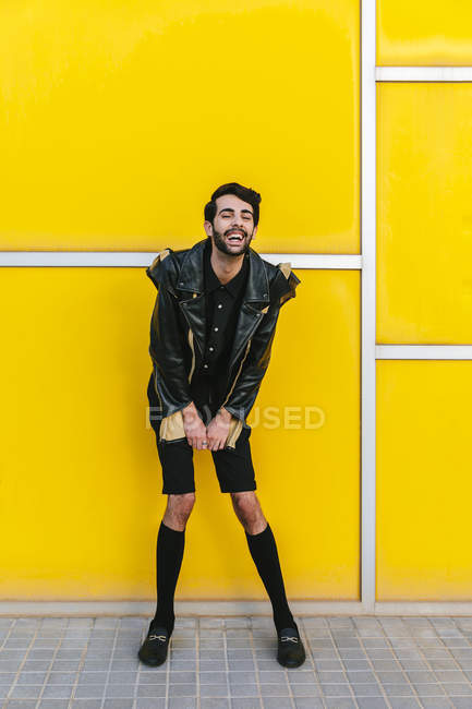 Laughing fashion man over yellow wall — Stock Photo