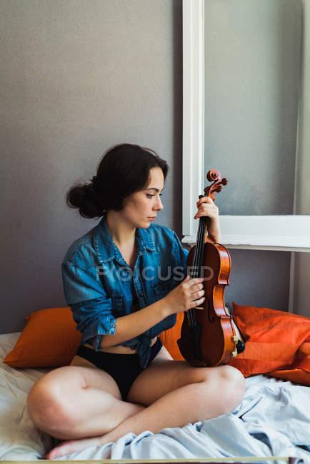 Beautiful woman sitting with violin — Stock Photo