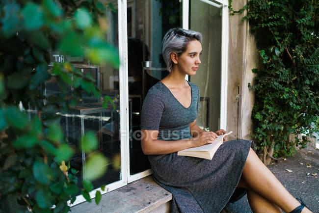 Lesebuch der Frau am Fenster — Stockfoto