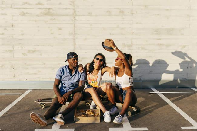 Freunde posieren auf Brettern und Pizza essen, in der Straße — Stockfoto