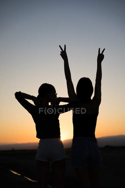 Silhouettes of women on beach — Stock Photo