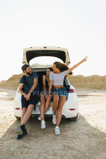Друзі, сидячи в багажник автомобіля — стокове фото