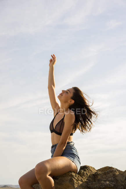 Woman relaxing on stone — Stock Photo