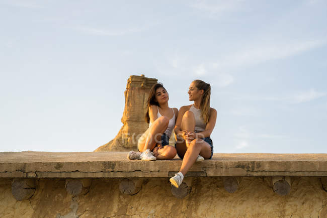 Pretty women sitting on roof — Stock Photo