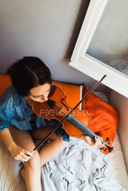 Frau spielt Geige im Bett — Stockfoto