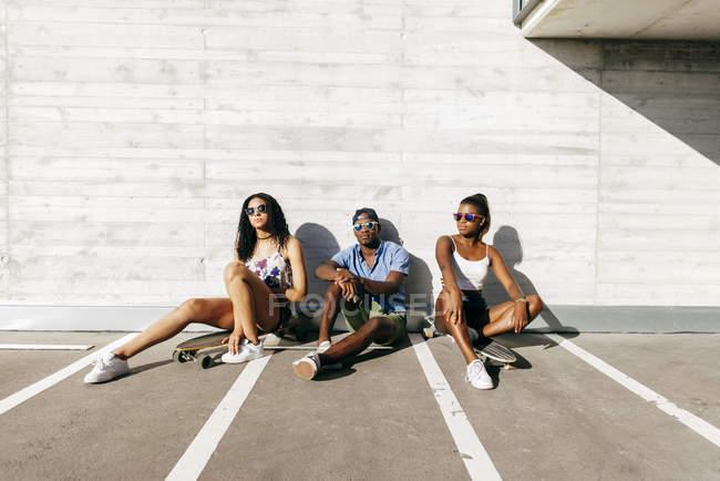Drei Jugendliche mit Brettern an der street — Stockfoto