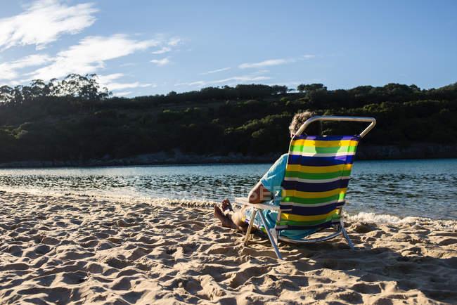Человек, сидя в красочных Председатель пляж — стоковое фото