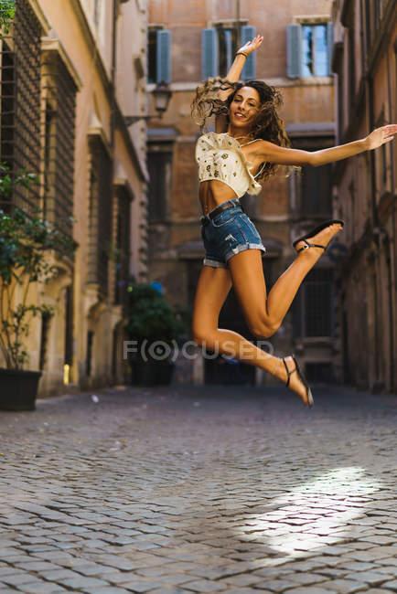 Adatto ragazza che salta in strada — Foto stock