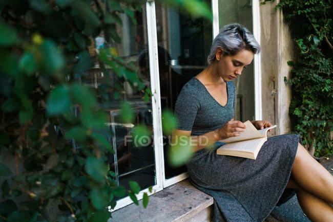 Livre de lecture femme à la fenêtre — Photo de stock