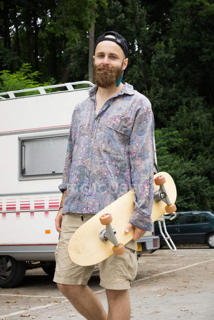 Man standing with skateboard — Stock Photo