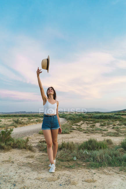Woman throwing up hat in nature — Stock Photo