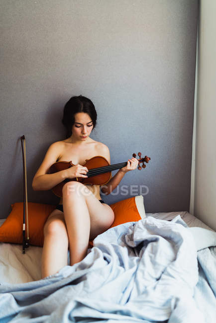 Naked woman posing with violin — Stock Photo