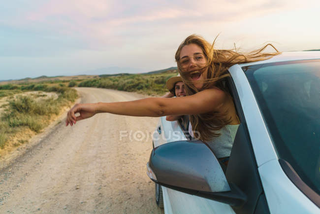 Women hanging out of car — Stock Photo