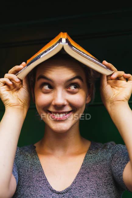 Очаровательная девушка позирует с книгой на голове — стоковое фото