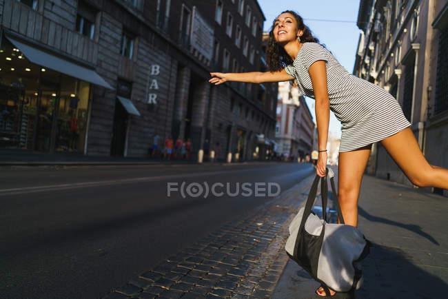 Girl hitchhiking on street road — Stock Photo