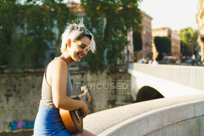 Girl playing small guitar at street — Stock Photo