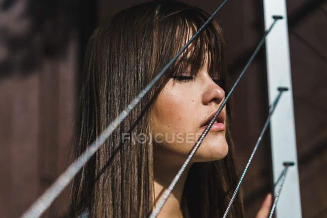 Donna in piedi alla recinzione corda con gli occhi chiusi — Foto stock