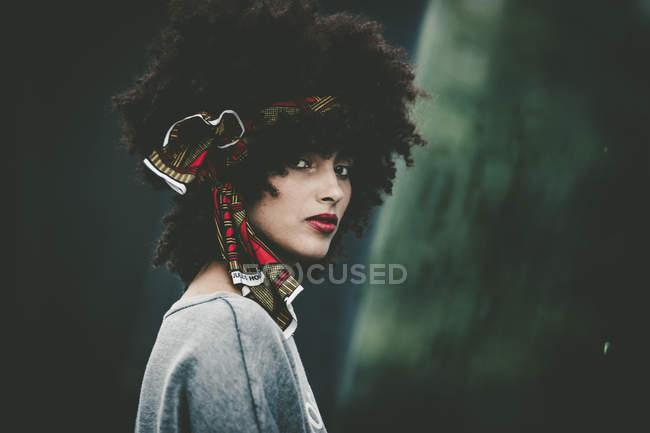 Portrait d'une femme élégante avec coupe de cheveux afro, regardant la caméra — Photo de stock
