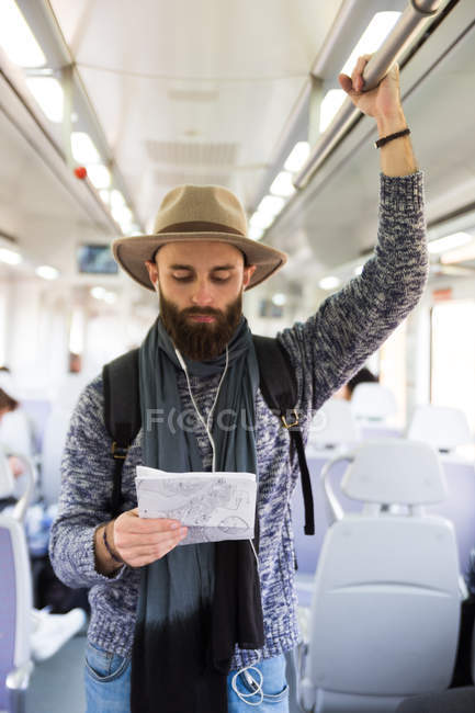 Portrait of bearded man in hat standing in train and looking down at map in hands — Stock Photo
