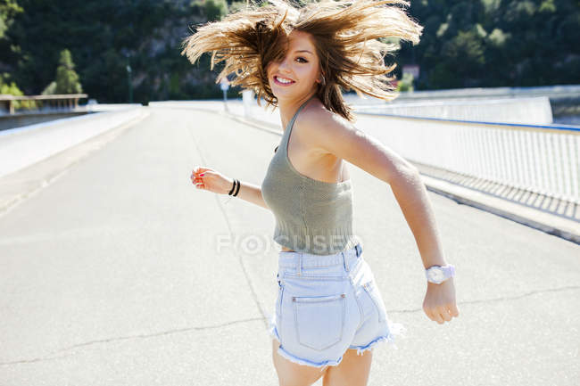 Laufenden Mädchen über die Schulter in die Kamera schaut — Stockfoto