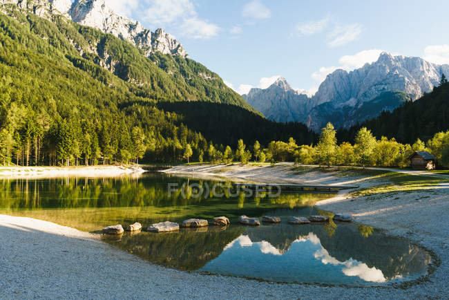 Picturesque landscape of small lake with reflection of trees on background of rocky mountain peaks. — Stock Photo