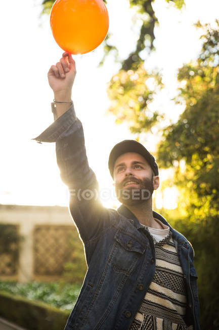 Uomo barbuto allegro in protezione che tiene Aerostato arancione sopra la testa e sorridere alla luce del sole. — Foto stock